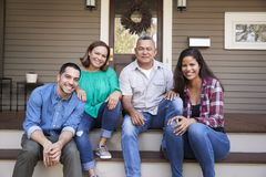 Parents With Adult Offspring Sitting On Steps in Front Of House stock photography