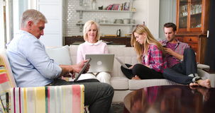 Parents With Adult Offspring Using Digital Devices At Home. Family with adult offspring sit on sofa using laptops, digital tablet and mobile phone together.Shot stock video footage