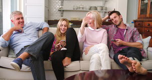 Parents With Adult Offspring Watching Television At Home. Family with adult offspring sit on sofa watching television whilst daughter uses mobile phone.Shot in stock video