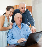 Parents with adult son in internet. Adult son halping his perents with laptop Royalty Free Stock Image