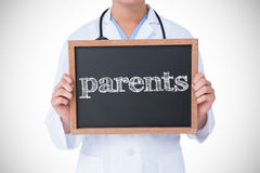 Parents against doctor showing little blackboard Royalty Free Stock Photo