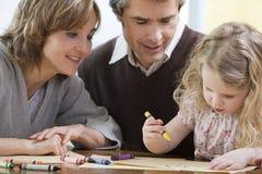 Parents aidant leur fille à dessiner Photo stock