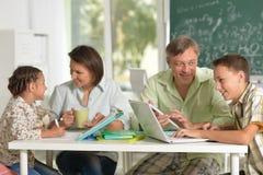 Parents aidant leurs enfants à faire leurs devoirs image libre de droits