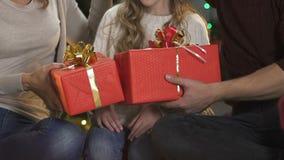 Parents aimants donnant à fille deux grands cadeaux de Noël, faisant la surprise, bonheur banque de vidéos
