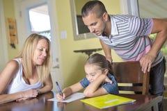 Parents al hijo de ayuda con la preparación en el interior casero Imagenes de archivo