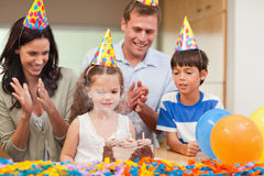 Parents applauding her daughter who just blew out the candles Stock Photography