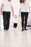 Parents apprendre leur beau bébé comment marcher Photographie stock libre de droits