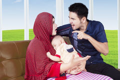 Parents arguing while carrying their baby. Portrait of young parents arguing at home while sitting on sofa and carrying their baby Stock Photos