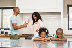 Parents arguing in front of children. In the kitchen Stock Photo