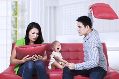 Parents Arguing. Scared baby sitting on the couch listening to parents argument Stock Photo