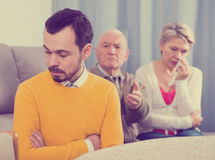 Parents arguing with son. Father and mother having disagreement with adult son at home Royalty Free Stock Photo