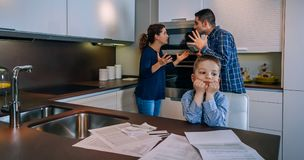 Parents arguing with their little son in front. Parents arguing heatedly in the kitchen with their little son in front stock photography