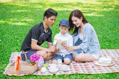 Parents as Teachers concept: Teen family with one kid happy education moment. In the park stock photos