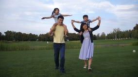 Parents asiatiques gais portant des enfants sur des épaules banque de vidéos