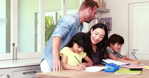 Parents assisting children doing homework. At home stock video