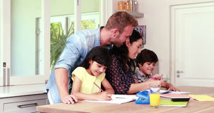 Parents assisting children doing homework. At home stock video footage