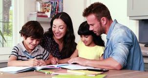 Parents assisting children doing homework stock video footage