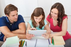 Parents assisting daughter in using digital tablet Stock Images