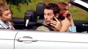 Parents au téléphone dans une voiture convertible banque de vidéos