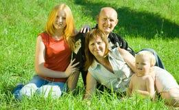 Parents avec des enfants dans l'herbe Photographie stock libre de droits
