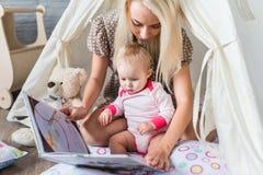 Parents avec des enfants dans un tipi Photographie stock libre de droits