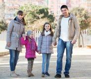 Parents avec des enfants marchant dans la rue Photographie stock libre de droits