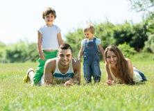 Parents avec des enfants s'étendant dans l'herbe Photos libres de droits