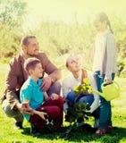 Parents avec deux enfants plantant un buisson Photographie stock
