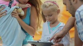 Parents avec deux petites filles s'asseyant sur un pique-nique clips vidéos