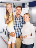 Parents avec la fille dans le magasin d'appareil ménager Photo libre de droits