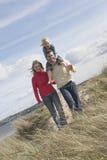 Parents avec la fille marchant sur la plage photos libres de droits