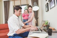 Parents avec la fille travaillant à côté des technologies à la table dans h Image stock