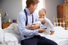 Parents avec le jeune bébé s'habillant pour le travail dans la chambre à coucher images libres de droits