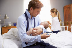 Parents avec le jeune bébé s'habillant pour le travail dans la chambre à coucher photos libres de droits
