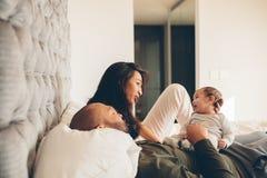 Parents avec le petit bébé garçon sur le lit Photos stock