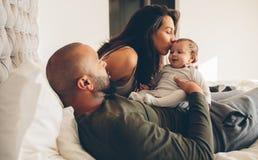 Parents avec leur bébé garçon nouveau-né sur le lit Image stock