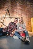 parents avec leur enfant sur le fond d'une étoile avec des ampoules Photographie stock