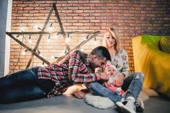 parents avec leur enfant sur le fond d'une étoile avec des ampoules Photographie stock libre de droits