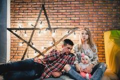 parents avec leur enfant sur le fond d'une étoile avec des ampoules Images stock