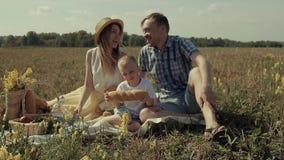 Parents avec leur fils prenant le déjeuner en nature un jour ensoleillé Petit garçon mangeant un morceau de pain clips vidéos