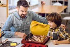 Parents avec plaisir positifs jouant des échecs Photos libres de droits