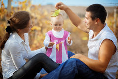 Parents with baby in autumn Stock Photos
