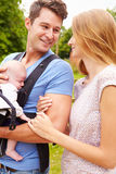 Parents With Baby In Carrier On Walk In Countryside Royalty Free Stock Image
