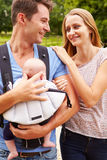 Parents With Baby In Carrier On Walk In Countryside Stock Photo