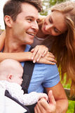 Parents With Baby In Carrier On Walk In Countryside Stock Image