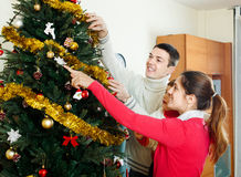 Parents and baby  decorating Christmas tree Stock Photo