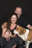 Parents with baby and dog. Portrait of young couple with two week old baby girl and pet dog, black background stock photo