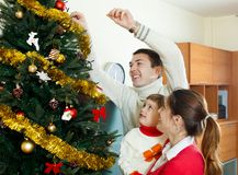 Parents and baby girl decorating Christmas tree Stock Photography