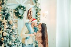 Parents and baby having fun near Christmas tree. Loving family by Christmas tree Royalty Free Stock Photography