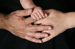 Parents and baby holding hands isolated on black